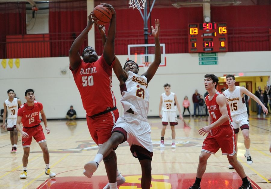 Schaumburg's Chris Hodges goes up against Palatine's Julian Campbell for the rebound in the varsity basketball matchup at Schaumburg on Friday.