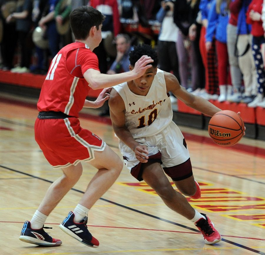 Mark Welsh/mwelsh@dailyherald.comSchaumburg's Vaurice Patterson drives against Palatine's Connor Aikman in the varsity basketball matchup at Schaumburg on Friday.
