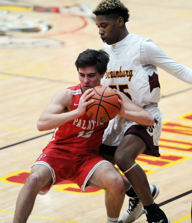 Mark Welsh/mwelsh@dailyherald.comSchaumburg's A.J. Prowell squares off against Palatine's Luke Seiffert in the varsity basketball matchup at Schaumburg on Friday.