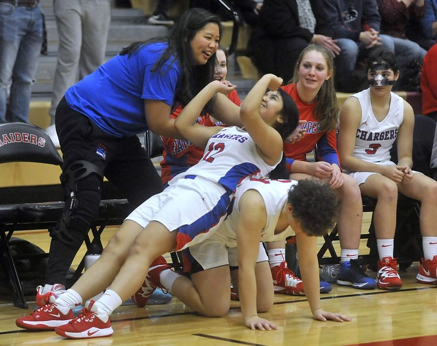 Dundee-Crown's Erica Sanchez pretends to bench press weights on top of her teammate, Alaina Azar, as they celebrate a score in the fourth quarter of a the IHSA Class 4A Sectional semifinal girls basketball game between Dundee-Crown and Huntley Tuesday evening, Feb. 25, 2020, at Huntley High School.