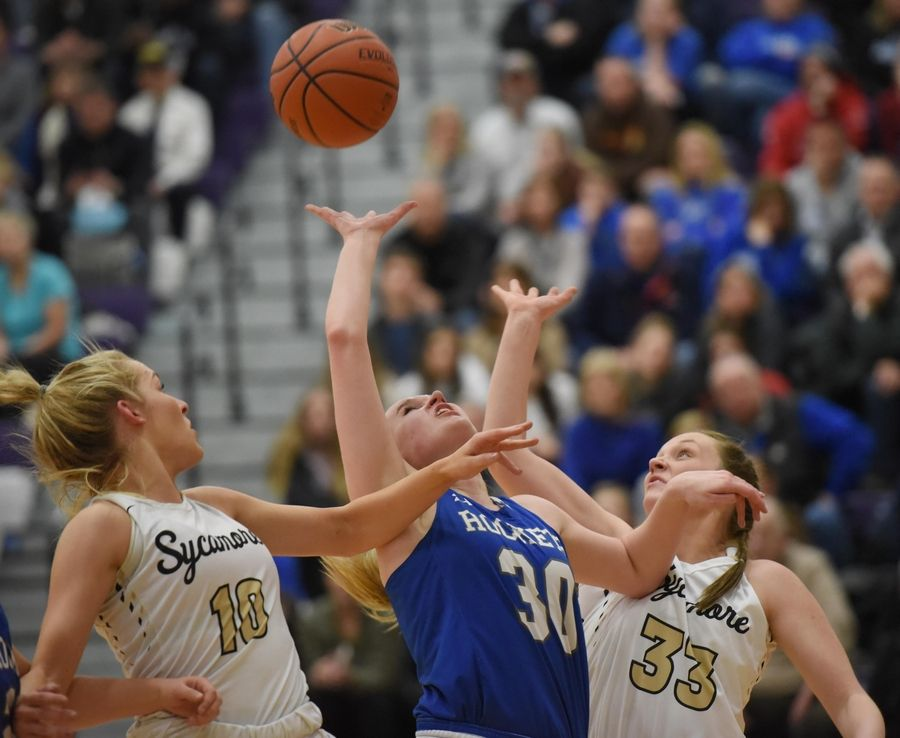 Burlington Central's Kathryn Schmidt and Sycamore's Kylie Feuerbach and Ella Shipley battle for a rebound in the Class 3A Hampshire girls basketball sectional semifinal game Tuesday.