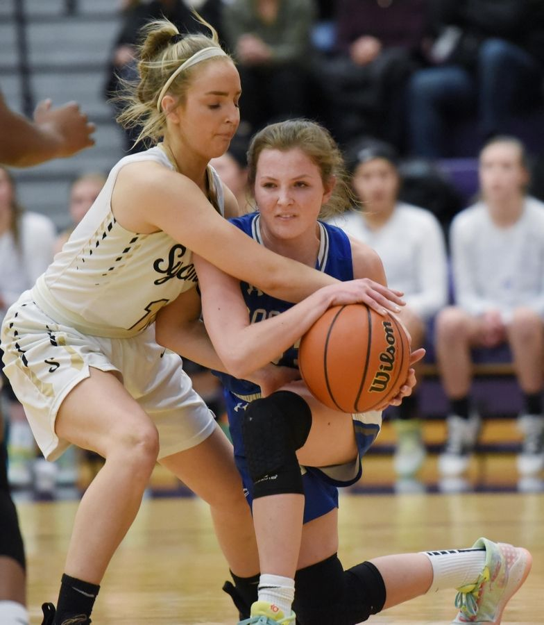 Sycamore's Faith Klemm closely defends Burlington Central's Madelyn Menke in the Class 3A Hampshire girls basketball sectional semifinal game Tuesday.