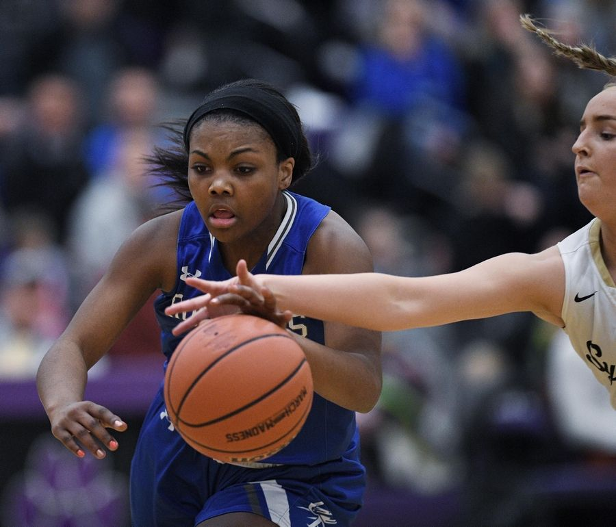 Burlington Central's Elana Wells reaches in to disrupt the dribble of Sycamore's Faith Klemm in the Class 3A Hampshire girls basketball sectional semifinal game Tuesday.