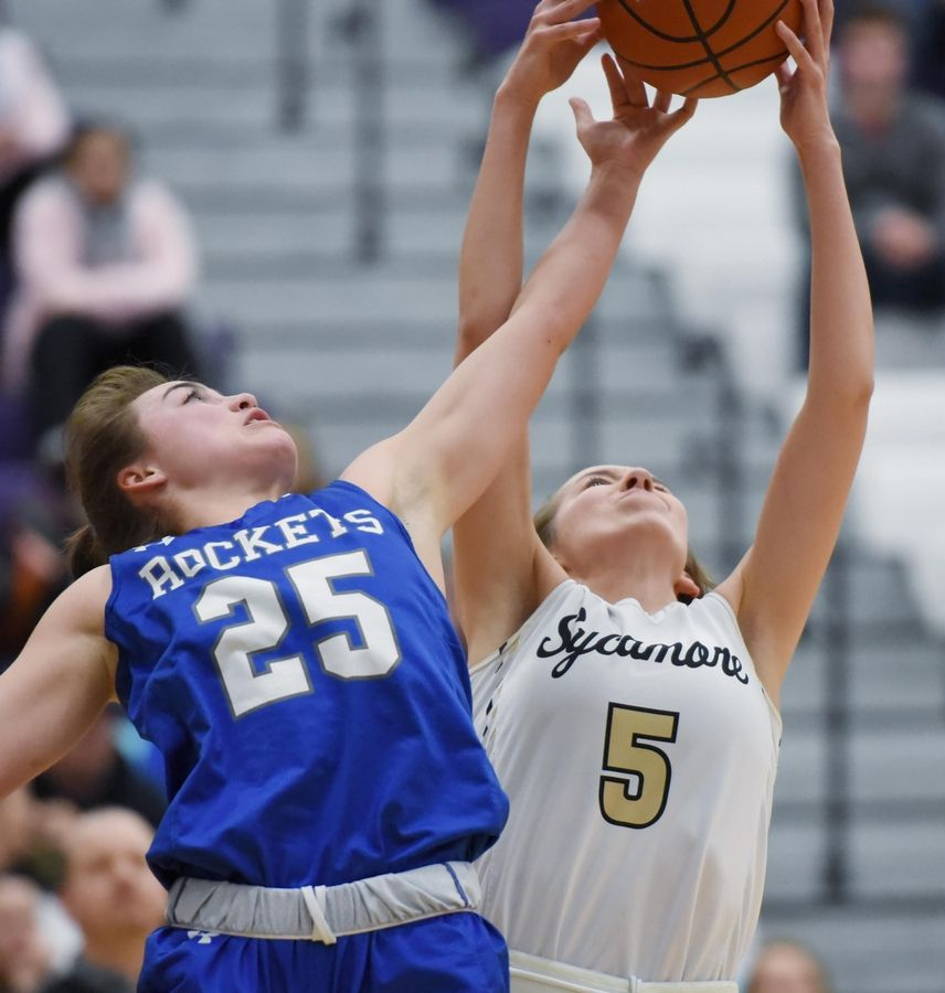 Burlington Central's Reili Gardner and Sycamore's Faith Feuerbach stretch for a rebound in the Class 3A Hampshire girls basketball sectional semifinal game Tuesday.
