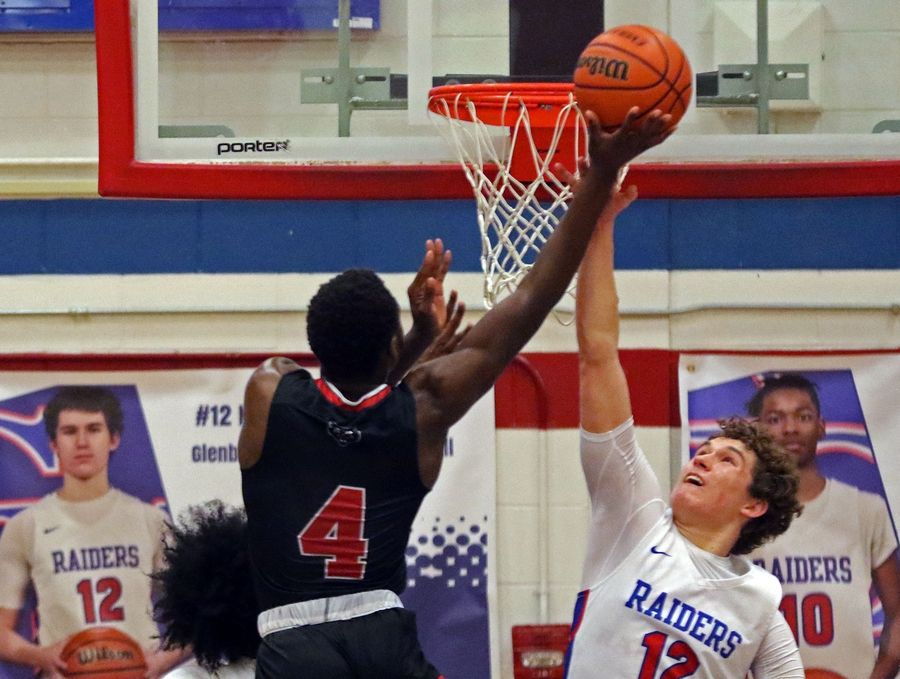 Glenbard South's Nick Plaso attempts to block an East Aurora shot during a game in Glen Ellyn on Feb. 26. The Raiders won 60-56.