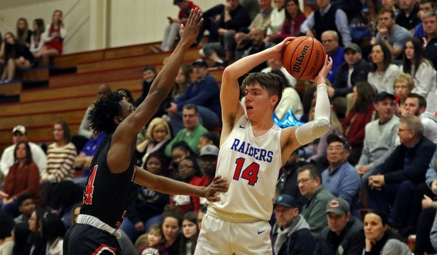 Glenbard South's Cade Hardtke looks to pass the basketball against East Aurora during a game in Glen Ellyn on Feb. 26. The Raiders won 60-56.