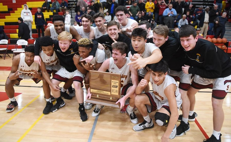 Schaumburg players celebrate with their trophy after defeating Buffalo Grove 49-43 in the Mid-Suburban League championship game at Schaumburg Wednesday.