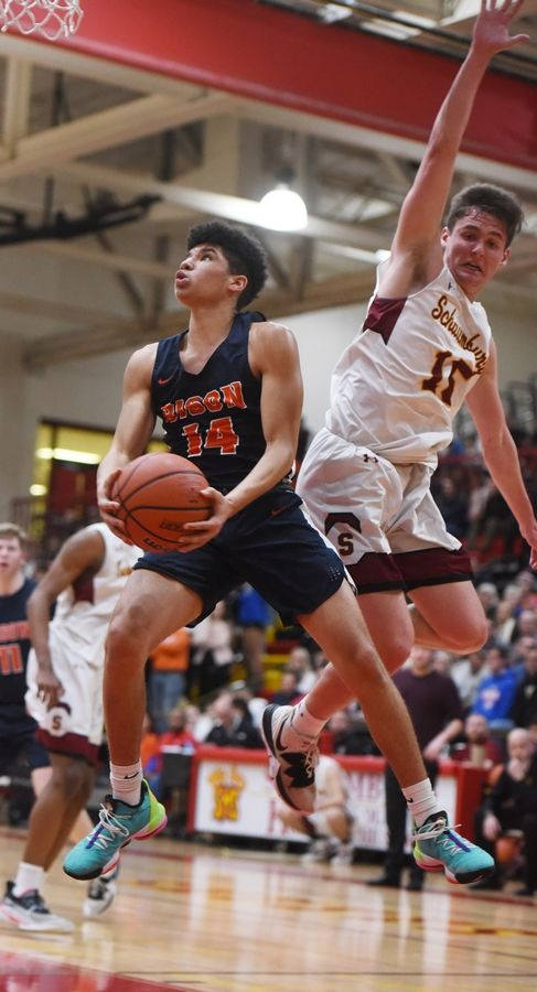 Buffalo Grove's Steph Harris drives to the basket for a layup in front of Schaumburg's Jared Schoo during the Mid-Suburban League championship game in Schaumburg Wednesday.