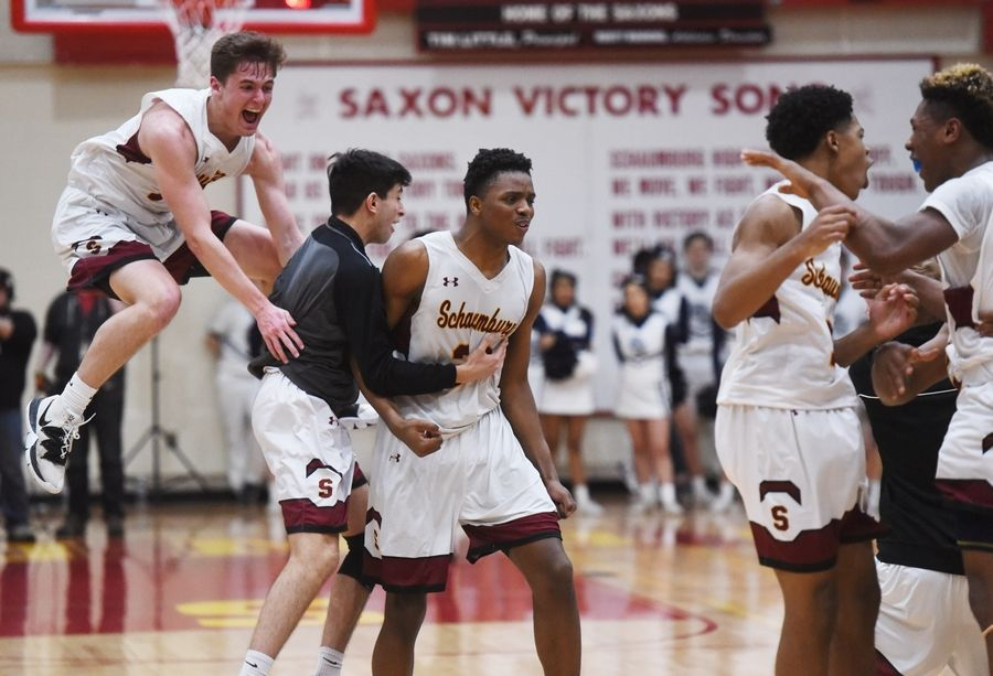 Schaumburg's Jared Schoo, left, and Chris Hodges, second from left, celebrate with their team after defeating Buffalo Grove 49-43 in the Mid-Suburban League championship game in Schaumburg Wednesday.