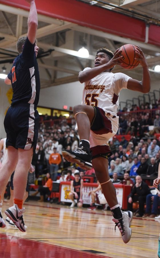 Schaumburg's A.J. Powell, right, drives to the basket for a layup against Buffalo Grove defender Nate Cole during the Mid-Suburban League championship game in Schaumburg Wednesday.