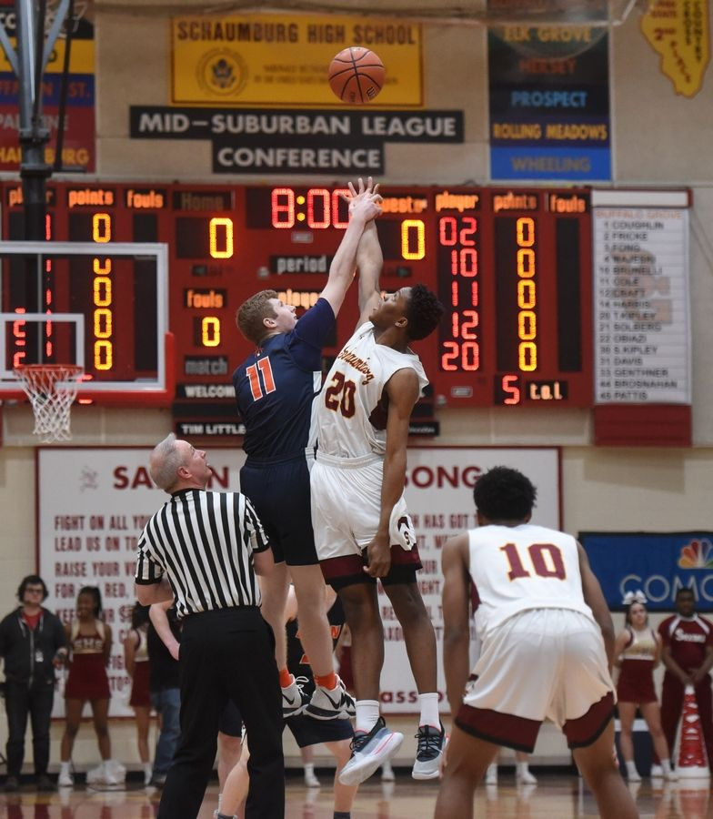 Buffalo Grove's Nate Cole, left, and Schaumburg's Chris Hodges leap for the ball at the opening tip-off to start the Mid-Suburban League championship game in Schaumburg Wednesday.