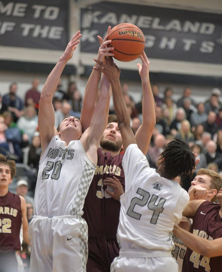 Kaneland's Porter Conroy, left, and Jamari Meeks battle Morris forward Sam Williams for a rebound in the second quarter of an Interstate 8 Conference matchup Friday in Maple Park.