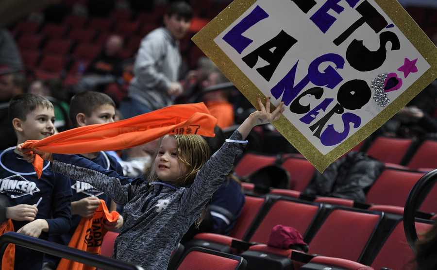 Lake Park fan Stella Mikes, 7, of Wheaton shows team spirit as she holds up her sign when the Lake Park players take the floor in the Class 4A state girls basketball semifinal game in Normal on Friday.