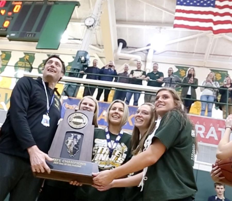 Fremd High School Principal Kurt Tenopir, left, accepts the state championship trophy from members of the girls basketball team Monday during a pep rally to celebrate the team's Class 4A title.
