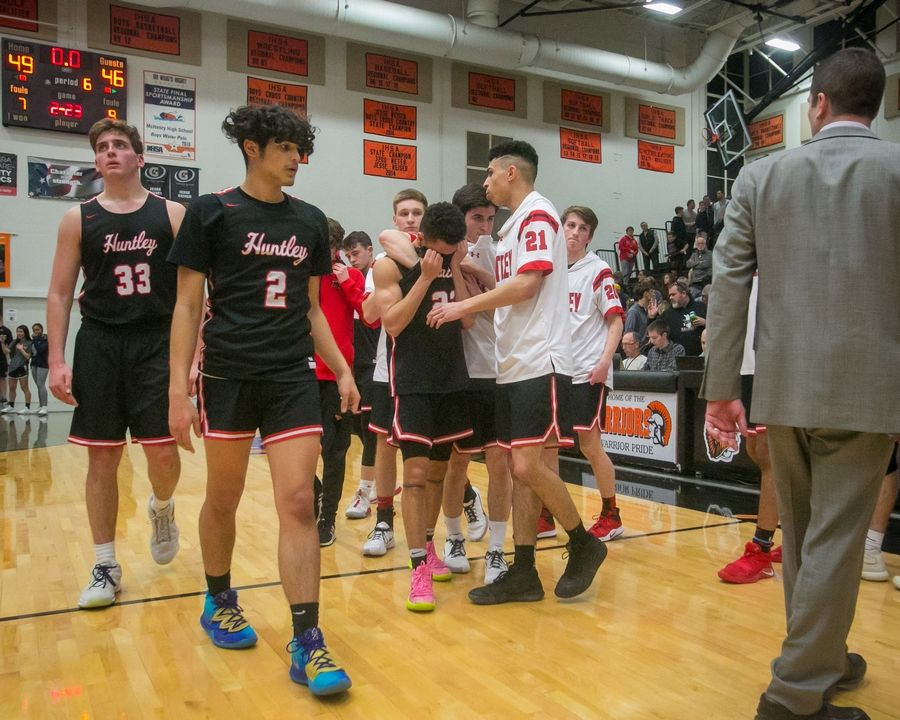 Huntley guard Ryan Crosby (23) is consoled by teammates after losing a double overtime game in the Class 4A McHenry sectional semifinals Tuesday to Cary-Grove.