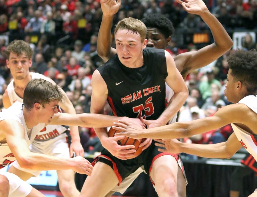 Indian Creek senior Cooper Larsen is surrounded by three Aurora Christian defenders Tuesday during their IHSA Class 1A DeKalb (NIU) Super-Sectional in the Convocation Center at Northern Illinois University.