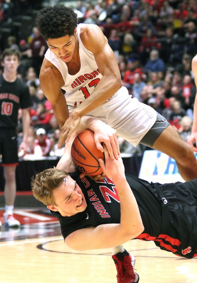 Aurora Christian senior Taaj Davis and Indian Creek senior Cooper Larsen fight for a loose ball Tuesday during their IHSA Class 1A DeKalb (NIU) Super-Sectional in the Convocation Center at Northern Illinois University.