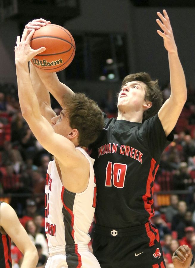 Indian Creek junior Brennen McNally grabs a rebound over Aurora Christian senior Karsen Olsen Tuesday during their IHSA Class 1A DeKalb (NIU) Super-Sectional in the Convocation Center at Northern Illinois University.