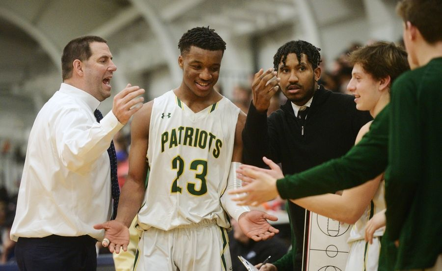 Stevenson's Robert Holmes is welcomed to the bench by coach Pat Ambrose and his teammates following a late substitution during the Prospect boys basketball sectional semifinal against Zion-Benton in Mount Prospect Tuesday.