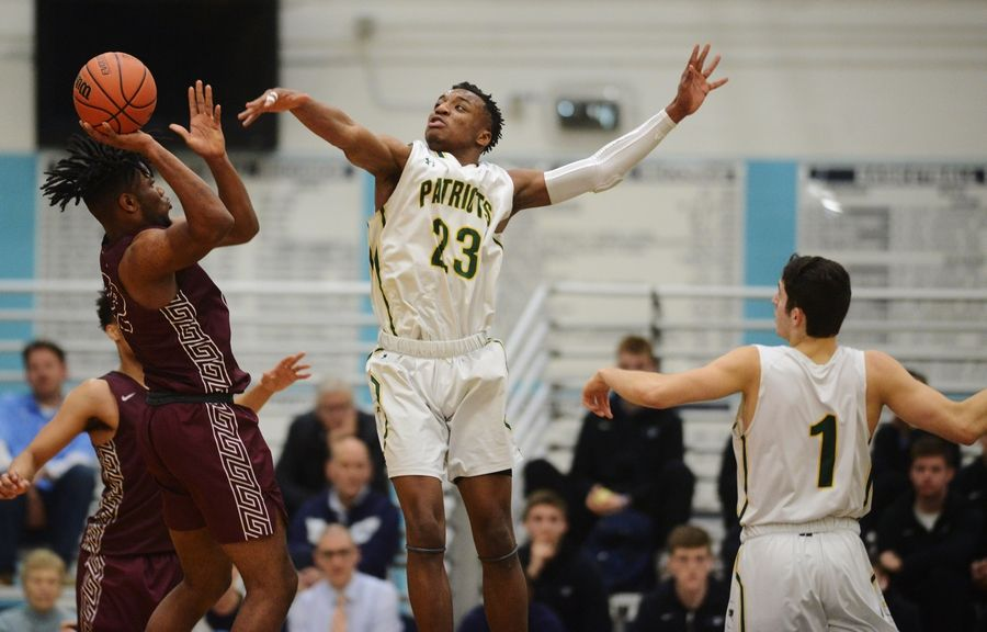 Stevenson's Robert Holmes, middle, and John Ittounas, right, defend a shot by Zion-Benton's Amar Augillard during game one of the Prospect boys basketball sectional semifinal in Mount Prospect Tuesday.