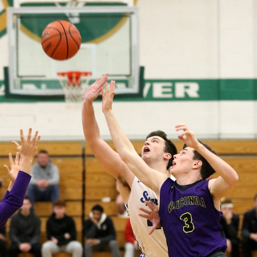 Wauconda's Nicholas Bulgarelli, right, and St. Francis' Bryce Walker go for the ball in Class 3A Rockford Boylan boys basketball sectional semifinal action Tuesday night.