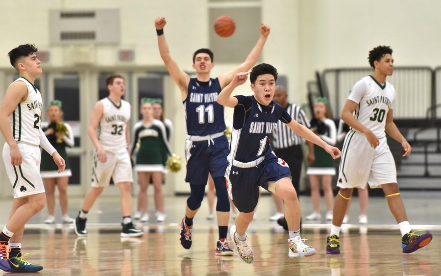 St. Viator's Eli Aldana (1) and Connor Kochera, background, react to their win against St. Patrick in a Class 3A sectional semifinal boys basketball game in Grayslake Wednesday.