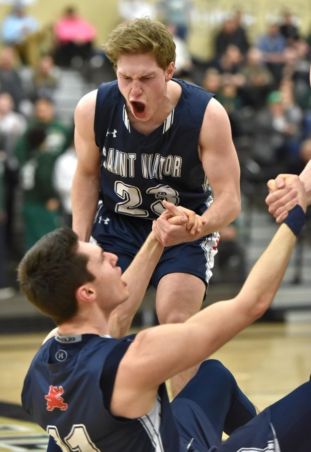 St. Viator's Patrick Schumacher reacts as he helps teammate Connor Kochera up from the floor after he was fouled while scoring late in overtime against St. Patrick in a Class 3A sectional semifinal boys basketball game in Grayslake Wednesday.