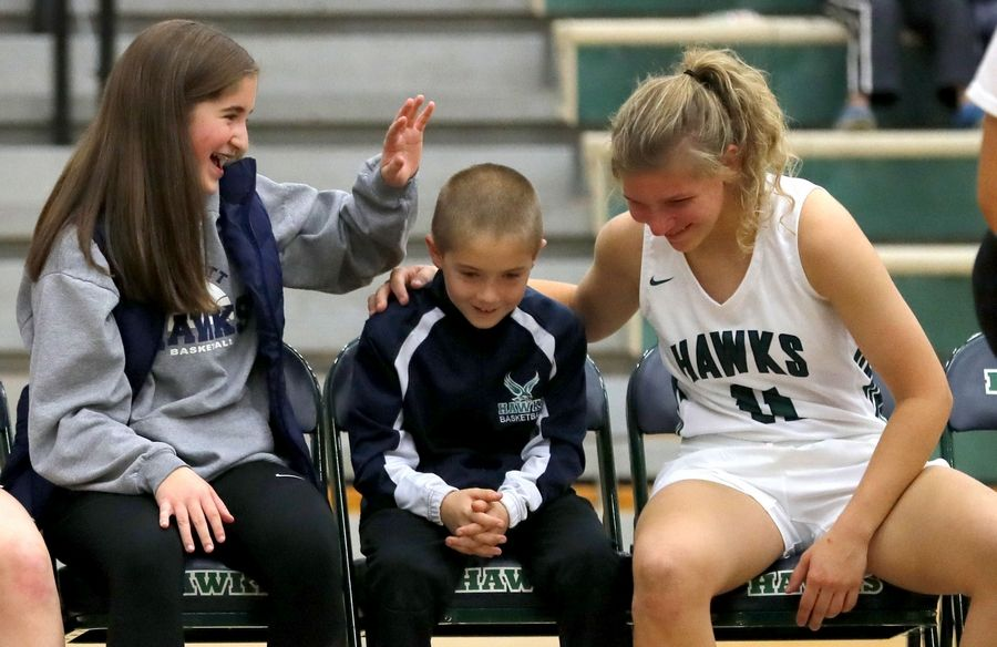 Former Bartlett girls basketball coach Brad Hunt was remembered with a brief memorial ceremony before this year's season opener against Fenton. Hunt's children Madison and Brady were involved in pregame lineup announcements as well as a ceremonial tipoff in memory of their dad, who died suddenly in June. Here, varsity player Lexie Sinclair shares a moment with the kids.