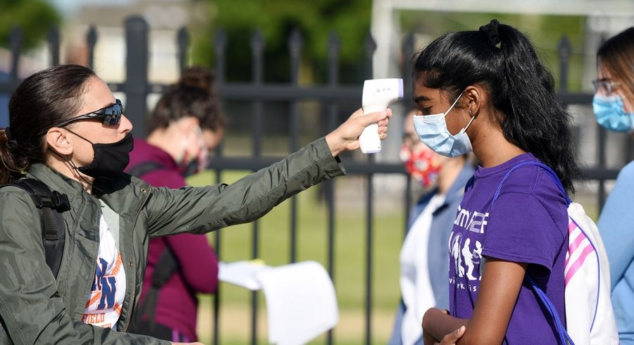 Naperville North field hockey coach Monica Lodge checks the temperature of sophomore lacrosse player Gautami Palthepu as part of the IHSA's Stage 1 return-to-play guidelines.