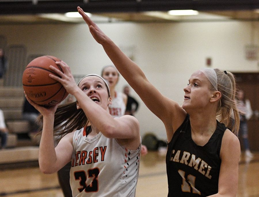 Hersey's Mary Kate Fahey eyes the basket despite pressure from Carmel's Katie Lach in a regional final game last season. Many schools are in the process of deciding whether to play this winter, against public health guidance, while most schools have decided not to play.