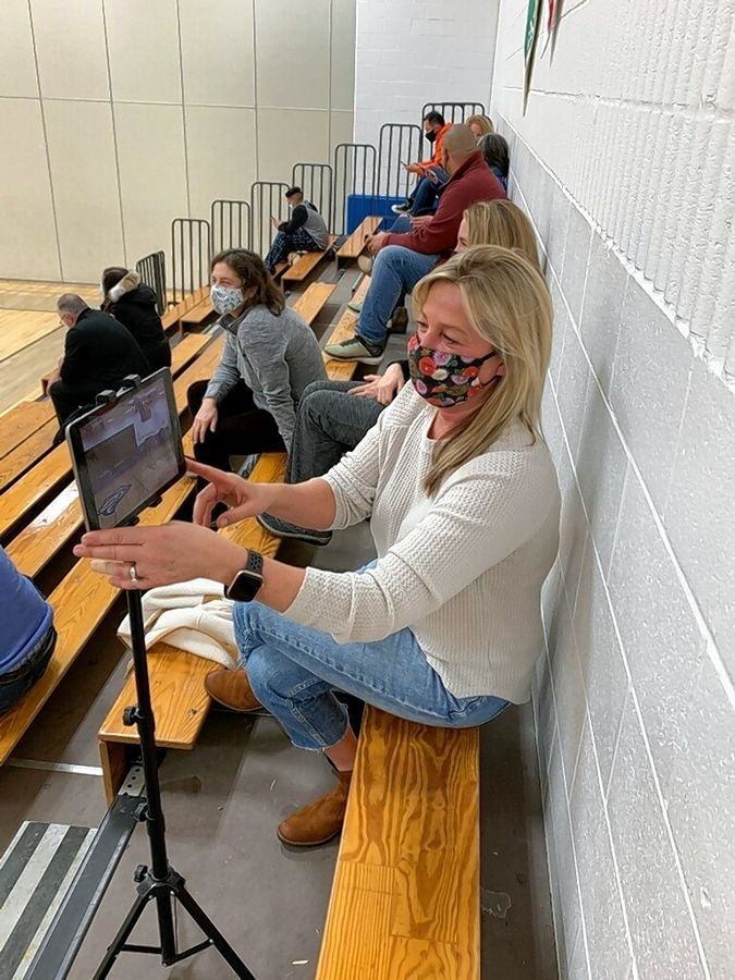 Stevenson High School basketball mom Joanne Porto films Wednesday's boys basketball game between the Patriots and Lake Forest for livestreaming on YouTube.