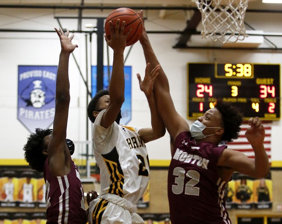 Morton's Dakari Durham (right) blocks Hinsdale South's Ahmad Tims during their basketball game at Hinsdale South High School in Darien, Ill., on Friday, Feb. 19, 2021.