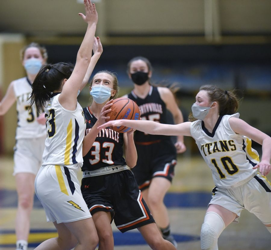 Libertyville's Morgan Spaulding scores against Glenbrook South's Marina Markovic and Sid Rogers, right, in a girls basketball game in Glenview Monday.