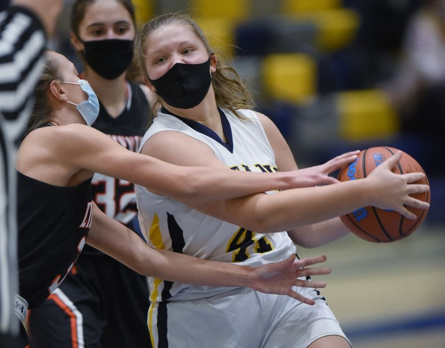 Glenbrook South's Caroline Adams is fouled by Libertyville's Morgan Spaulding in a girls basketball game in Glenview Monday, March 1, 2021.