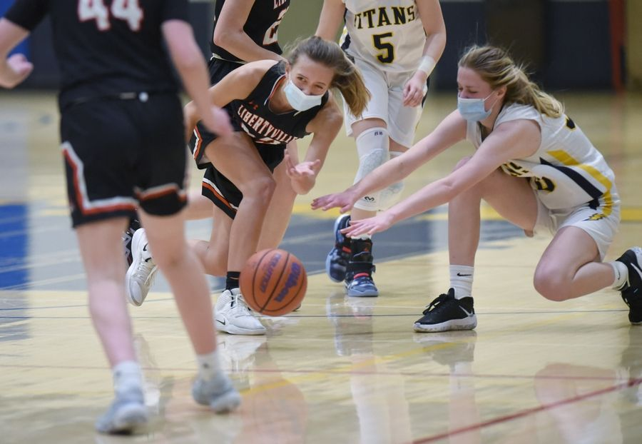 Libertyville's Morgan Spaulding scoops and passes the ball to teammate Lauren Huber in a girls basketball game against Glenbrook South in Glenview Monday, March 1, 2021.