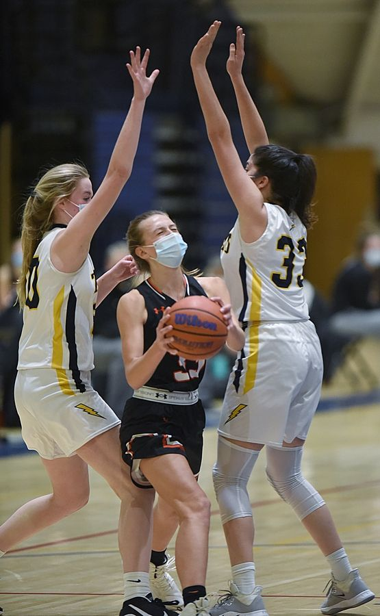 Libertyville's Morgan Spaulding gets through Glenbrook South's Anna Rosenberger and Marina Markovic, right, during Mondy night's game in Glenview.